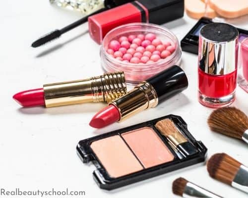 Make up assortment in hues of red and pinks including lipstick, blush, lip gloss and nail polish representing luxury, high end makeup.