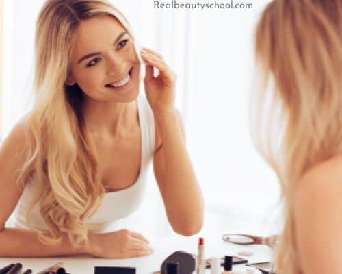Women sitting in front of a mirror getting ready to apply drugstore make up to her face, happy with her choice in deciding to go with drugstore makeup vs high end more expensive makeup brands.